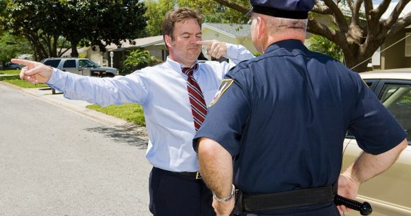 Police officer giving a roadside sobriety test to a drunk driver.