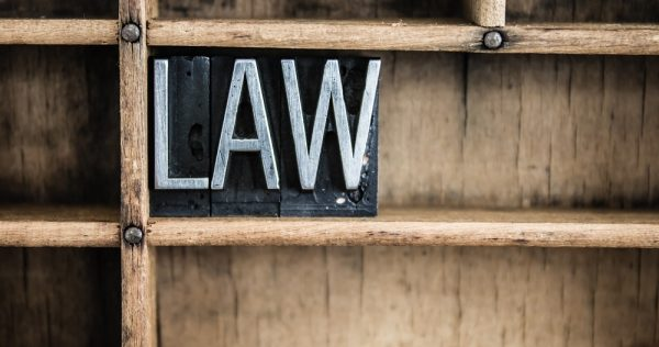 """The word """"LAW"""" written in vintage metal letterpress type in a wooden drawer with dividers."""