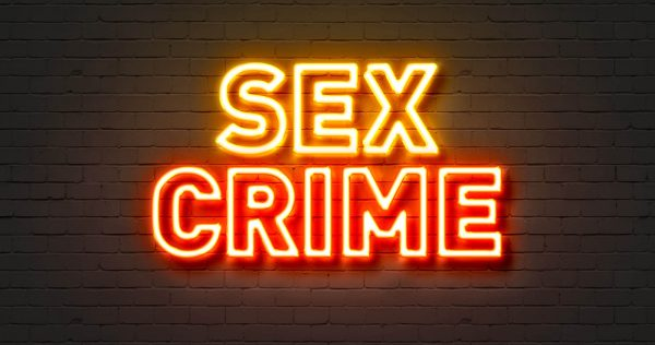 Sex crime neon sign on brick wall background